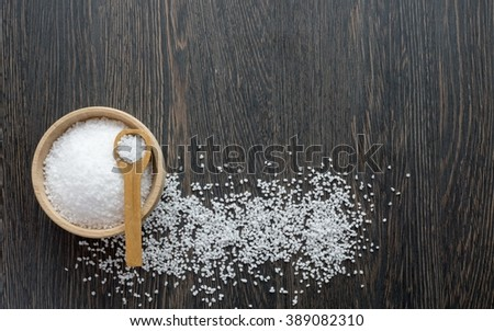 A wooden bowl of salt crystals on a wooden background