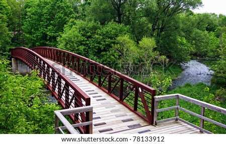 a wooden bridge leading into a forest - stock photo