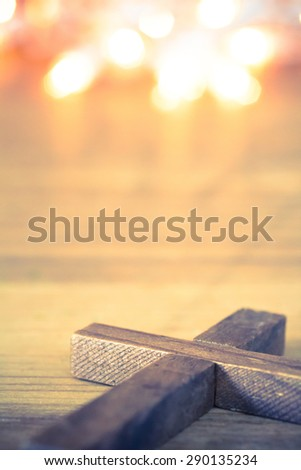 A wooden Christian cross laying on softly lit background. Room for copy. - stock photo