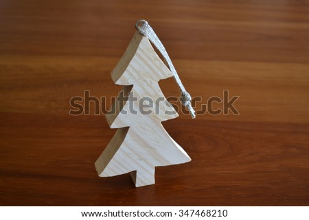 A wooden Christmas decoration standing on a wooden table. - stock photo