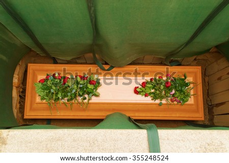 A wooden coffin covered with red roses in an open grave at a funeral. Green curtains cover the sides of the grave. Coffin is made of cherry wood. - stock photo