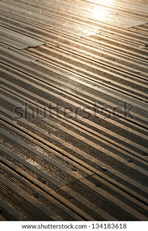 A wooden deck completely soaked wet, depicting the late afternoon yellow sun reflected as blown highlights.