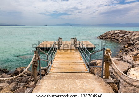 A wooden deck with metal railing on the shores of the Red sea - stock photo