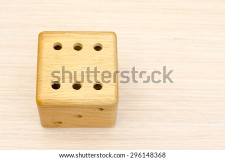 A wooden dice on a wooden table. The number fell to six