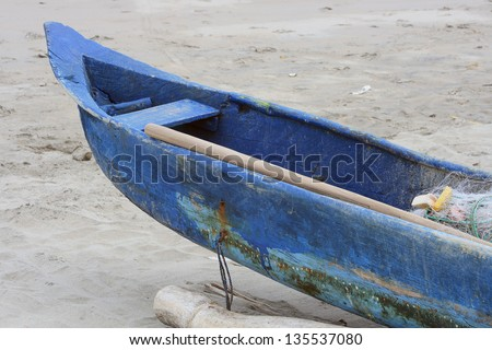 A wooden dugout fishing boat on the shore of the Pacific Ocean in Tonsupa, Ecuador