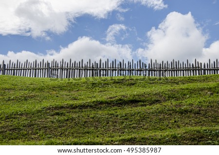 a wooden fence divide a green mountain field from the blue sky