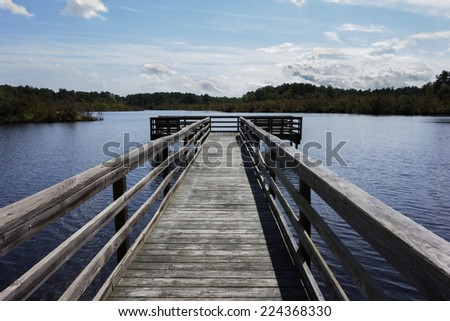 A wooden fishing dock over the water at Prime Hook National Wildlife Refuge in Milton, Delaware. - stock photo