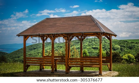 A wooden gazebo in summer city park.