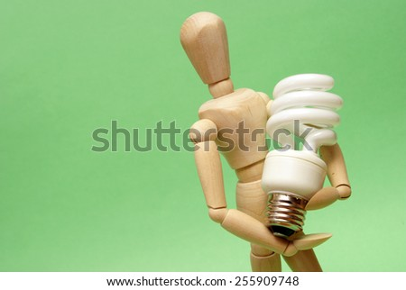 A wooden guy holds onto a modern cfl lightbulb for many ecological concepts. - stock photo