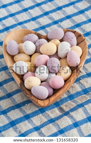 A wooden heart full of mini chocolate Easter eggs on a blue and white table cloth - stock photo