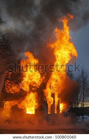 A Wooden house in flames - stock photo