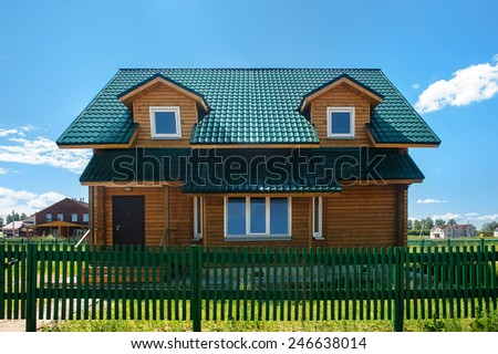 A wooden house with green roof in suburban neighborhood - stock photo