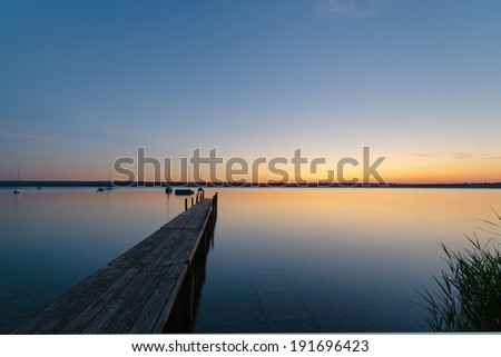 A wooden jetty and sailboats photographed at Breitenbrunn at lake Ammersee in Upper Bavaria.