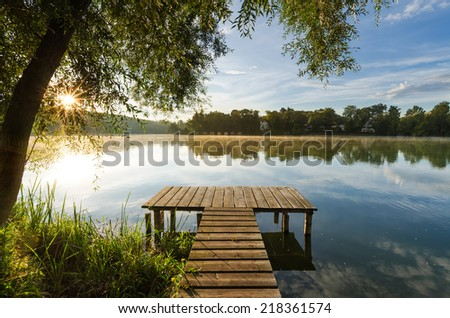 A wooden jetty at lake Wesslinger See at sunrise with sunstar - stock photo