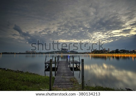 A wooden jetty at lake with  sunset scenery in the background, Soft Focus due to Long Exposure Shot. shoot at Putrajaya, Malaysia.