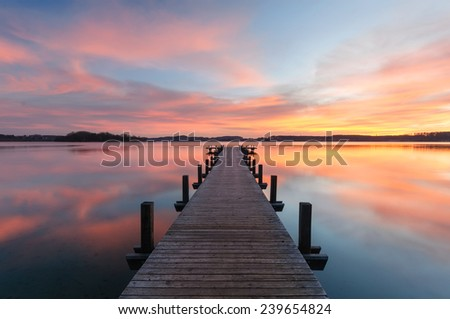 A wooden jetty at lake Woerthsee photographed early in the morning. - stock photo