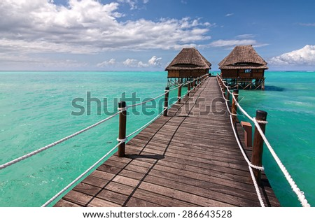 a wooden jetty leading to read huts the sea with a distant horizon aqua sea and cloudy sky - stock photo