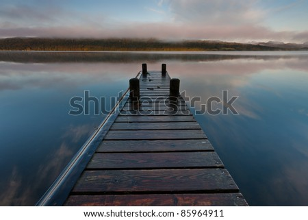 A wooden jetty on Lake Windermere one peaceful autumn morning with the Langdales in the background