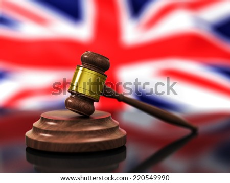 A Wooden Judge Gavel in Focus and Flag of United Kingdom Waving in Background - stock photo