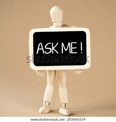 A wooden man holds a slate ready to deliver your message.Ask me - stock photo