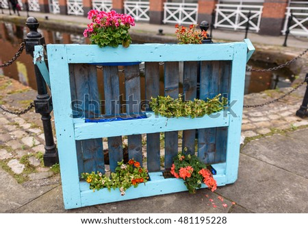 A wooden palette made into a floral display along a canal.