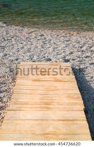 A wooden path leads to the sea - stock photo