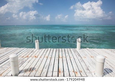 A wooden pier is used for tourist boats that bring divers and snorkelers to Halfmoon Caye off the coast of Belize. The island is near the blue hole and home to booby and frigate bird colonies. - stock photo
