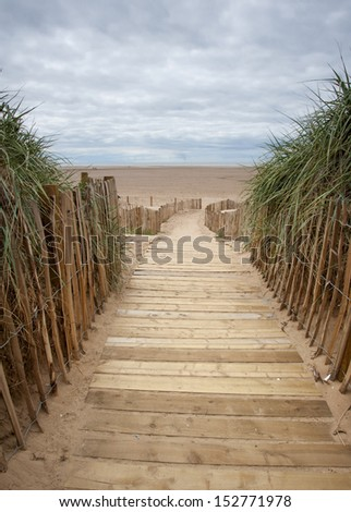 A wooden planked walkway to a beach on a cloudy day - stock photo