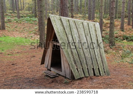 A Wooden Play Shelter in a Woodland Setting. - stock photo