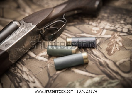 A wooden retro shotgun with shotgun shells - stock photo