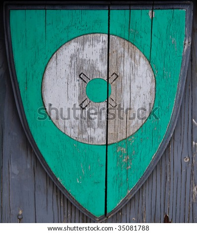 A wooden shield bears a symbolic wheel as the historic emblem of a Norwegian community.