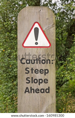 A wooden sign warning drivers that there is a steep slope ahead  - stock photo