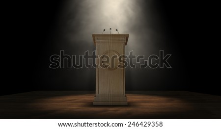A wooden speech podium with three small microphones attached on a dark background spotlit by a single spotlight - stock photo
