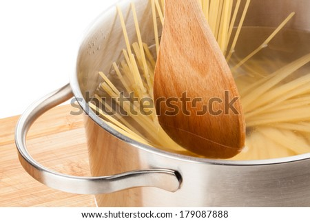 A wooden spoon is stirring some pasta in a pan which is filled with hot water. - stock photo