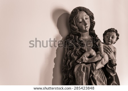 A wooden statue of Virgin Mary Madonna with a Child Jesus with different shades on the wall - stock photo