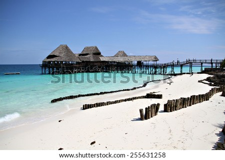 A wooden structure stands above the sea water on a beautiful beach on a luxury beach resort in paradise. - stock photo