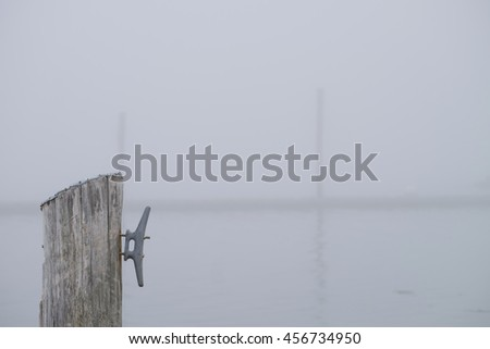 A wooden tie-up for boats on a foggy morning on the new england coast - stock photo
