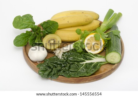 A wooden tray with Alkaline diet vegetables and fruits: Banana, kiwi, spinach, lemon, cucumber, parsley , silver beat and garlic. concept photo - stock photo