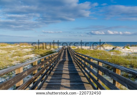 A wooden walkway to the Gulf of Mexico on the Alabama Gulf Coast. - stock photo