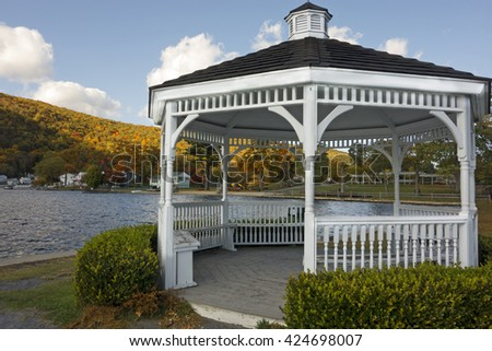 A wooden white gazebo on the lake in Autumn.