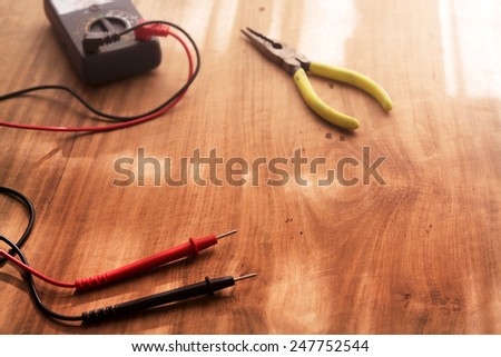A wooden work desk with an electric circuit tester, and a needle nose pliers. Focus is on foreground. - stock photo