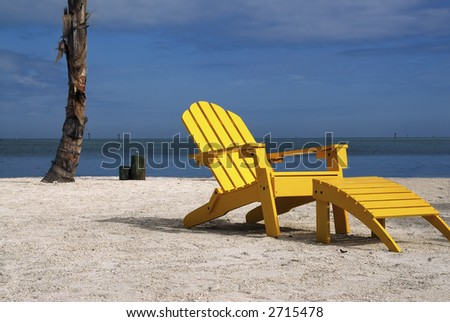 A wooden yellow recliner sits on a beautiful tropical beach