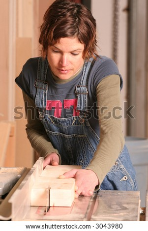 A woodworker sawing a pine board.