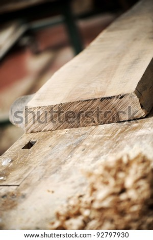 a work table of a carpenter with a wooden plank and a pile of wood chips - stock photo