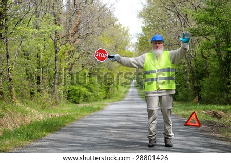 A worker blocks the access of the road. - stock photo