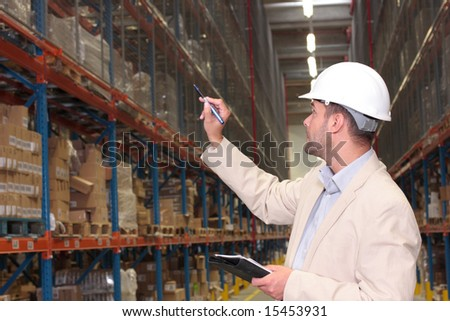 A worker counting the ready products stacked on the shelves in a factory storeroom. - stock photo