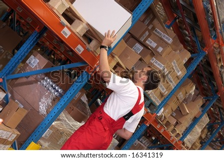 A worker in a factory keeping packages of finished products on the shelves in a storeroom. - stock photo