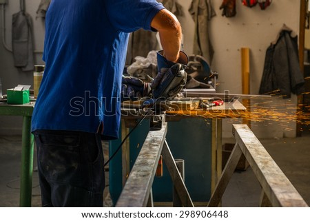 A worker using electric wheel grinding on steel structure in factory