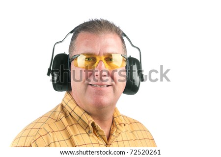 A worker wearing yellow safety glasses and hearing protection.