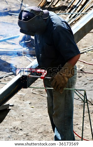 A worker welds two pieces of steel together using basic welding equipment